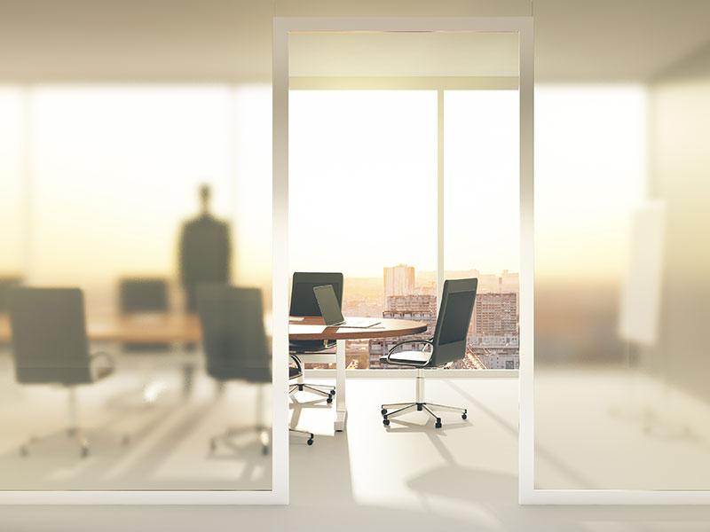 Mann steht in einem großen hellen Büro.