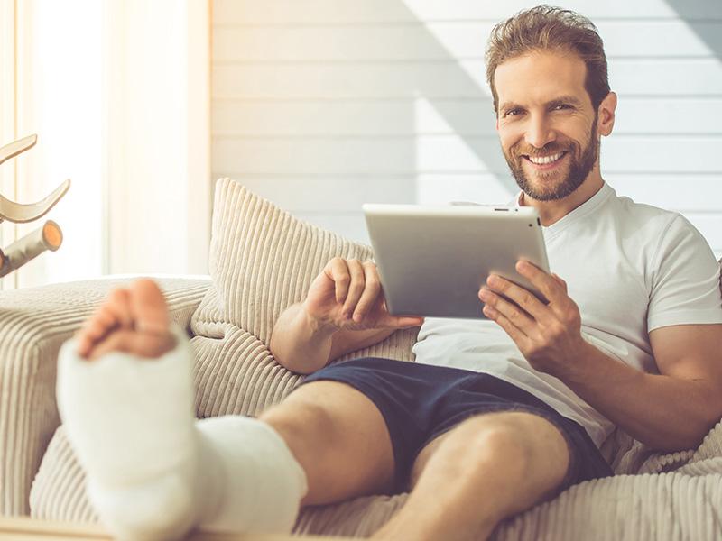Junger Mann in Unterwäsche liegt mit eingegipstem Fuß und Tablet auf Sofa