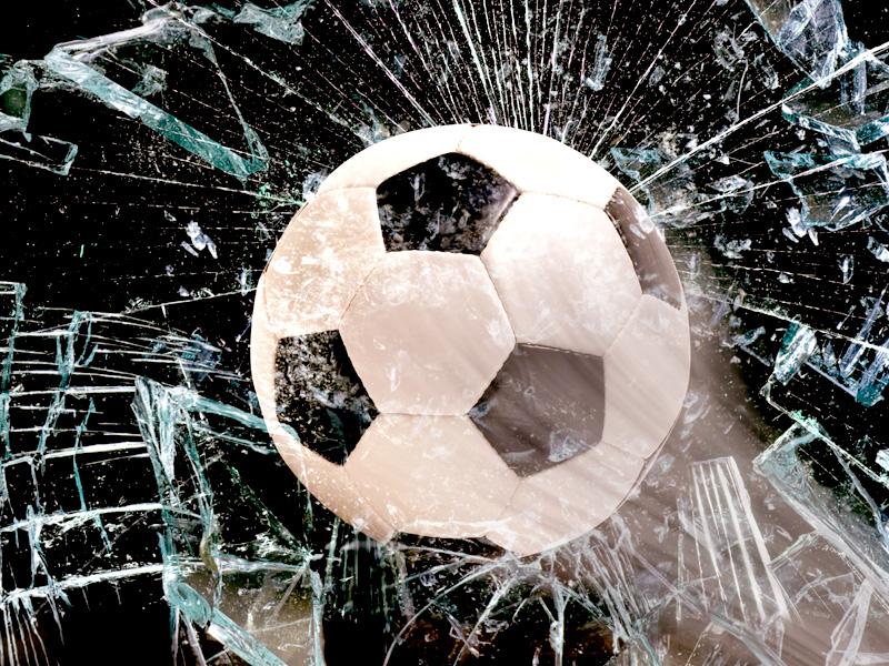 Fußball fliegt durch eine Fensterscheibe
